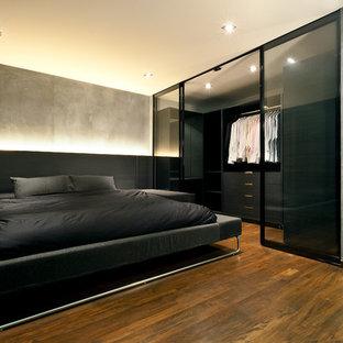 Ejemplo de dormitorio urbano con paredes grises y suelo de madera oscura