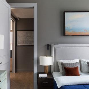 Стильный дизайн: хозяйская спальня в современном стиле с серыми стенами, паркетным полом среднего тона, коричневым полом и правильным освещением - последний тренд