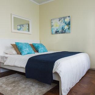 Modelo de dormitorio principal, nórdico, con paredes amarillas y suelo de madera en tonos medios
