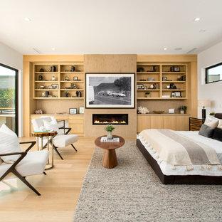 Inredning av ett modernt stort huvudsovrum, med vita väggar, ljust trägolv, en bred öppen spis, en spiselkrans i metall och beiget golv