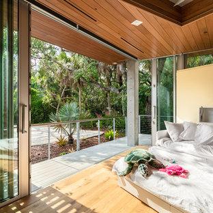 Modelo de dormitorio urbano con paredes beige, suelo de madera clara y suelo beige