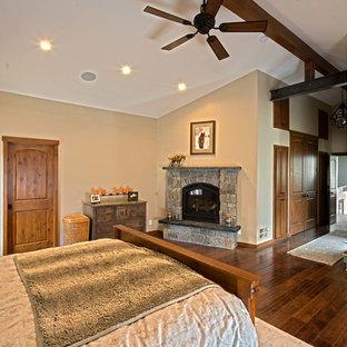 Immagine di una grande camera matrimoniale stile americano con pareti beige, parquet scuro, camino classico, cornice del camino in pietra e pavimento marrone
