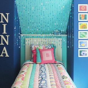 Modelo de habitación de invitados actual, pequeña, sin chimenea, con paredes azules y suelo de madera clara