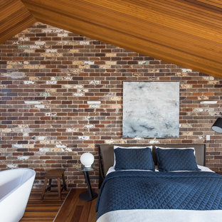 Design ideas for a large industrial master bedroom in Sydney with medium hardwood floors and no fireplace.