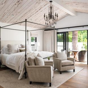 Großes Landhaus Hauptschlafzimmer mit weißer Wandfarbe, braunem Holzboden und braunem Boden in Phoenix