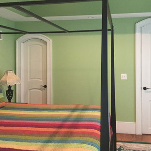 This is an example of a traditional master bedroom in Other with green walls, medium hardwood floors and brown floor.