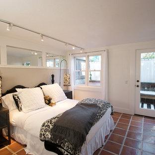 Cette photo montre une chambre éclectique avec un mur beige, un sol en carreau de terre cuite et un sol rouge.