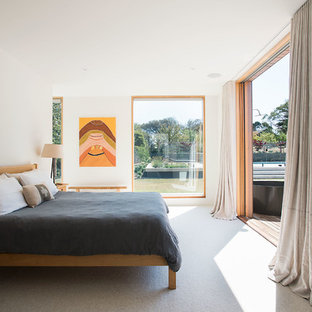 This is an example of a contemporary bedroom in Melbourne with white walls, carpet and grey floor.