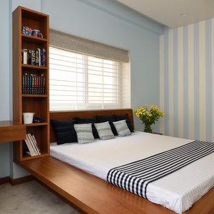 Esempio di una camera da letto design di medie dimensioni con pareti blu e pavimento grigio