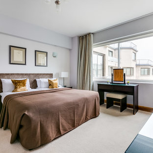 Design ideas for a traditional master bedroom in London with white walls, carpet and beige floors.