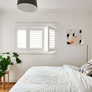 Photo of a contemporary bedroom in Melbourne with white walls, medium hardwood floors and brown floor.