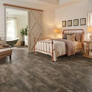 Diseño de dormitorio principal, de estilo de casa de campo, grande, sin chimenea, con paredes blancas, suelo vinílico y suelo marrón