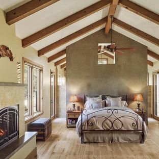 Ejemplo de dormitorio rústico con paredes beige, suelo de madera clara, chimenea tradicional y suelo beige