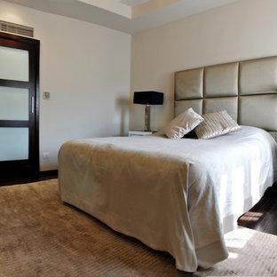 Ejemplo de dormitorio principal, contemporáneo, de tamaño medio, con paredes beige, suelo de contrachapado y suelo marrón