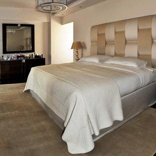 Foto di una camera matrimoniale minimal di medie dimensioni con pareti beige, pavimento in compensato e pavimento marrone