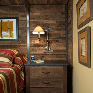 Imagen de dormitorio principal, rústico, de tamaño medio, sin chimenea, con paredes amarillas, moqueta y suelo gris