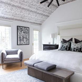 Réalisation d'une chambre tradition avec un mur blanc, un sol en bois brun et un sol marron.
