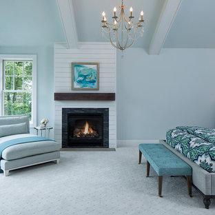 ミネアポリスのビーチスタイルのおしゃれな主寝室 (青い壁、カーペット敷き、標準型暖炉、木材の暖炉まわり)