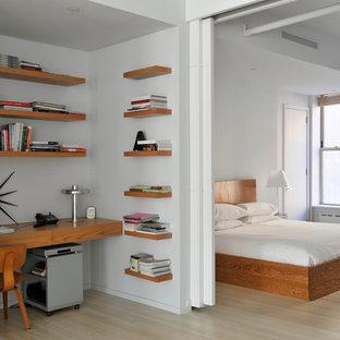 Idee per una camera da letto design con pareti bianche, parquet chiaro e angolo studio
