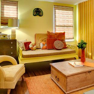 Imagen de dormitorio tipo loft, ecléctico, pequeño, sin chimenea, con paredes amarillas y suelo de madera en tonos medios