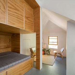 Bild på ett mellanstort funkis sovloft, med vita väggar, plywoodgolv och grått golv