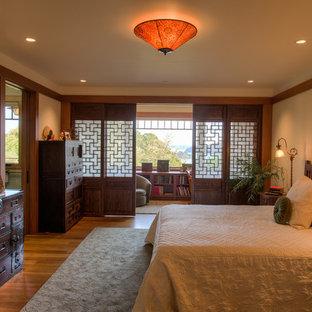 Immagine di una camera matrimoniale etnica con pareti beige, pavimento in legno massello medio e nessun camino