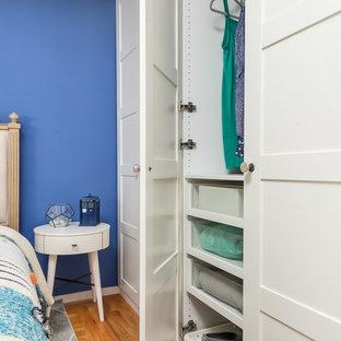 Imagen de habitación de invitados ecléctica, pequeña, sin chimenea, con paredes azules, suelo de madera clara y suelo naranja