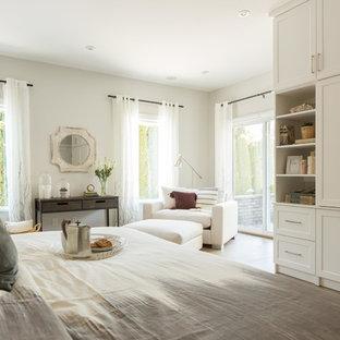 Inredning av ett klassiskt stort huvudsovrum, med vita väggar, ljust trägolv och beiget golv