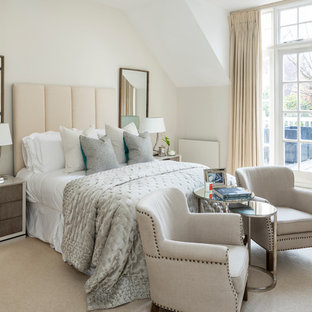 Photo of a traditional bedroom in London with white walls, carpet and beige floors.