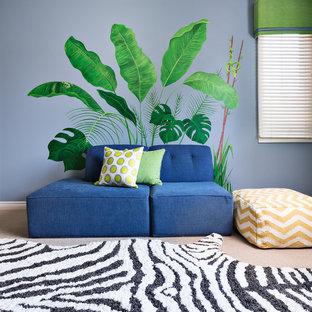 Imagen de dormitorio tipo loft, tropical, grande, sin chimenea, con paredes azules y moqueta
