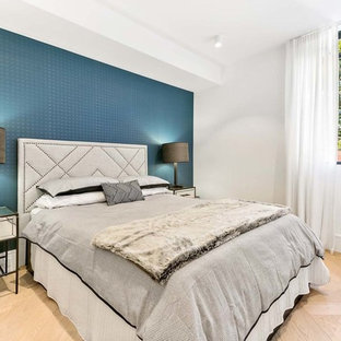 Design ideas for a mid-sized contemporary master bedroom in Sydney with light hardwood floors, beige floor and white walls.