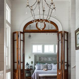 Coastal dark wood floor and brown floor bedroom photo in New Orleans with white walls