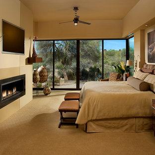 Ispirazione per una camera matrimoniale american style con pareti beige, moquette e camino lineare Ribbon