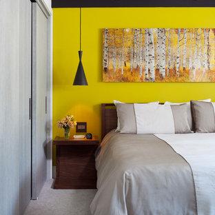 Kleines Mid-Century Hauptschlafzimmer ohne Kamin mit gelber Wandfarbe und Teppichboden in Denver