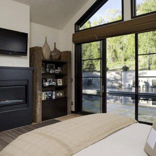 Modelo de dormitorio tipo loft, rural, de tamaño medio, con paredes blancas, suelo de madera clara, chimenea tradicional y marco de chimenea de yeso