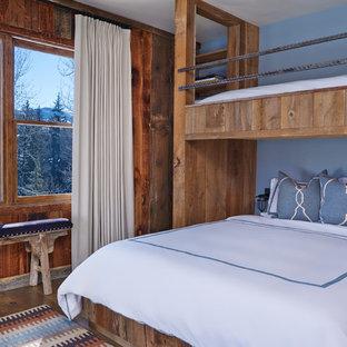 Imagen de habitación de invitados rústica con paredes azules y suelo de madera en tonos medios