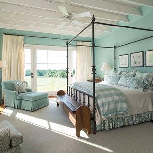 Modelo de dormitorio campestre con paredes azules, suelo de madera oscura, chimenea tradicional y marco de chimenea de ladrillo