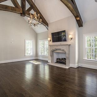 Diseño de dormitorio principal, de estilo americano, grande, con paredes blancas, suelo de madera oscura, chimenea tradicional y marco de chimenea de hormigón