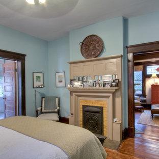 Foto de dormitorio de estilo americano con paredes azules, suelo de madera en tonos medios, chimenea tradicional y marco de chimenea de baldosas y/o azulejos