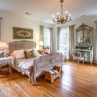Inspiration for a large timeless guest medium tone wood floor bedroom remodel in Atlanta with white walls and no fireplace