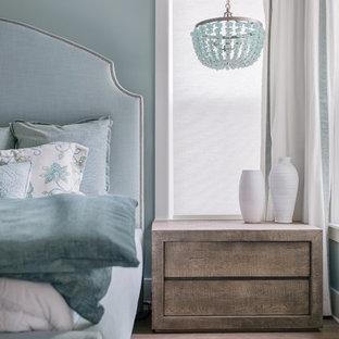 Imagen de dormitorio principal, marinero, grande, con paredes azules, suelo de baldosas de cerámica y suelo marrón
