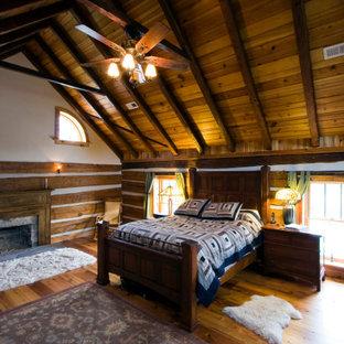 Foto de dormitorio abovedado y madera, rural, grande, madera, con paredes marrones, suelo de madera clara, chimenea tradicional, marco de chimenea de madera y madera