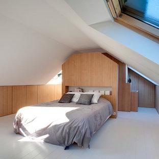 Exemple d'une grande chambre mansardée ou avec mezzanine tendance avec un mur blanc, un sol en bois peint et aucune cheminée.