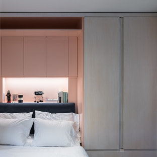 This is an example of a small modern master bedroom in New York with pink walls and dark hardwood floors.