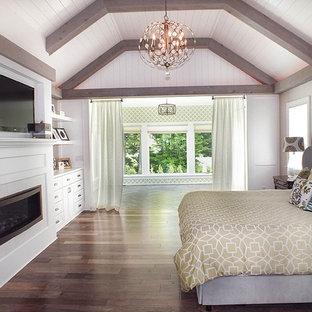 クリーブランドの広いモダンスタイルのおしゃれな主寝室 (白い壁、濃色無垢フローリング、標準型暖炉、木材の暖炉まわり、茶色い床) のレイアウト