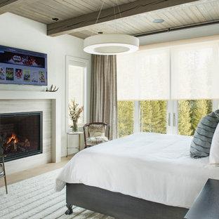 Стильный дизайн: хозяйская спальня среднего размера в стиле рустика с бежевыми стенами, светлым паркетным полом, стандартным камином, фасадом камина из плитки и коричневым полом - последний тренд