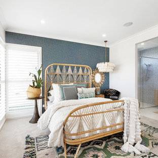 This is an example of a beach style master bedroom in Melbourne with blue walls, carpet and beige floor.