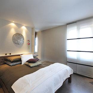 Ispirazione per una camera da letto etnica con pavimento in cemento e pavimento grigio