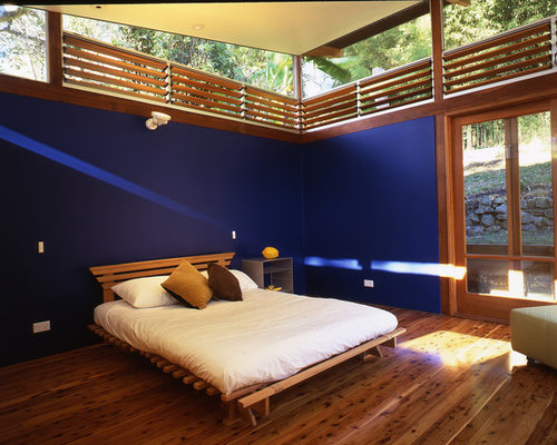 example of a coastal bedroom design in sydney with blue walls - Louvered Bedroom Decor