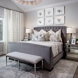 Modelo de dormitorio principal, contemporáneo, grande, con paredes grises, suelo de madera en tonos medios y chimenea lineal